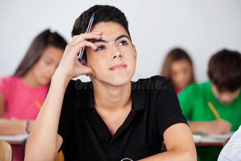 Nadenkende Jongen die omhoog in Klaslokaal kijken royalty-vrije stock foto