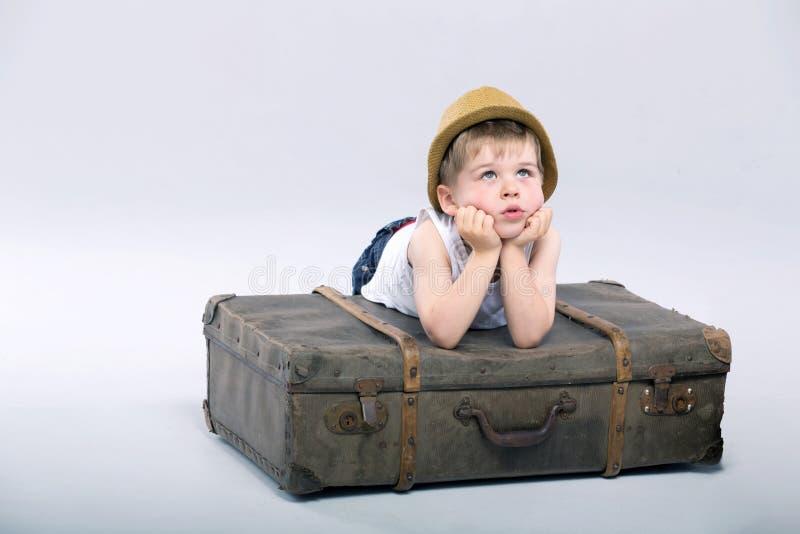 Nadenkende jongen die op de koffer liggen royalty-vrije stock afbeeldingen