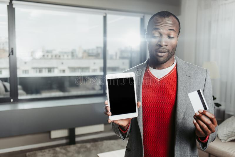 Nadenkende kerel die zich binnen met tablet en creditcard bevinden stock afbeeldingen