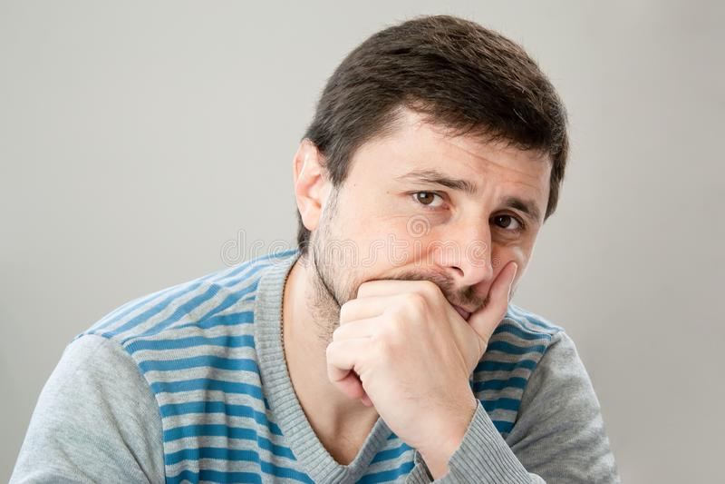 Nadenkende knappe gebaarde mens in een gestreepte sweater die zijn hoofd leunen tegen zijn hand die de camera bekijken stock afbeeldingen