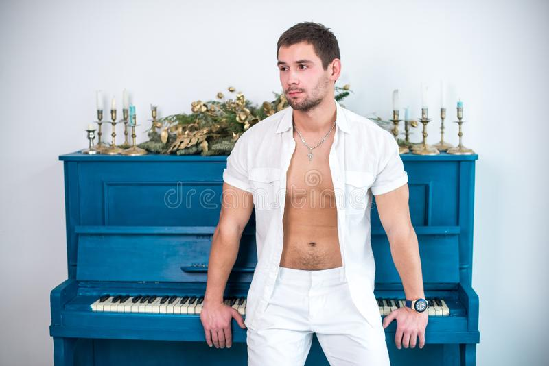 Nadenkende, knappe mens met een baard in witte kleren tegen de achtergrond van een piano, een geraspt overhemd met een naakt tors royalty-vrije stock foto's