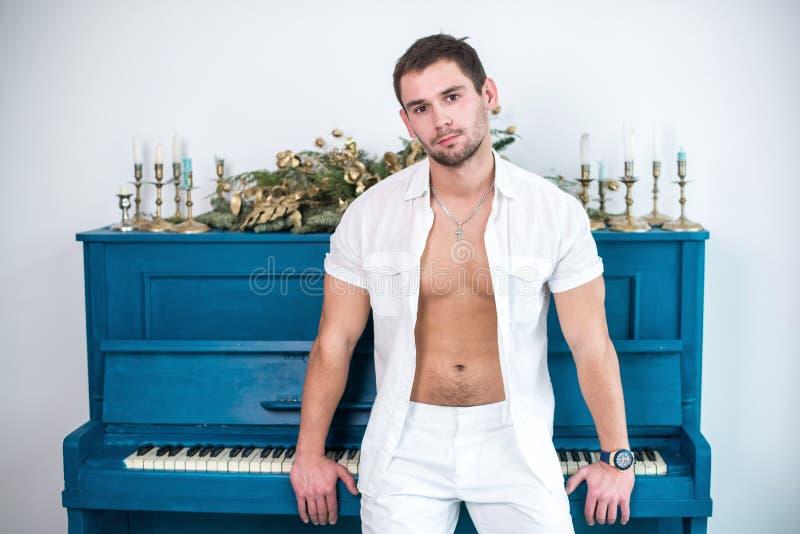 Nadenkende, knappe mens met een baard in witte kleren tegen de achtergrond van een piano, een geraspt overhemd met een naakt tors royalty-vrije stock afbeeldingen