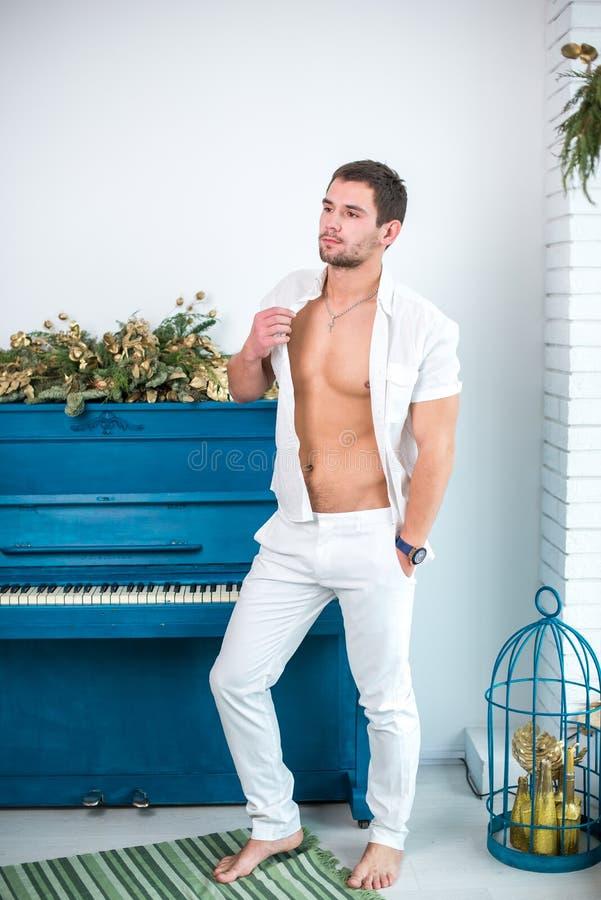 Nadenkende, knappe mens met een baard in witte kleren tegen de achtergrond van een piano, een geraspt overhemd met een naakt tors royalty-vrije stock afbeelding