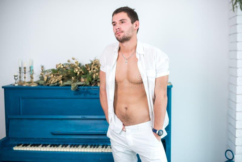 Nadenkende, knappe mens met een baard in witte kleren tegen de achtergrond van een piano, een geraspt overhemd met een naakt tors royalty-vrije stock fotografie