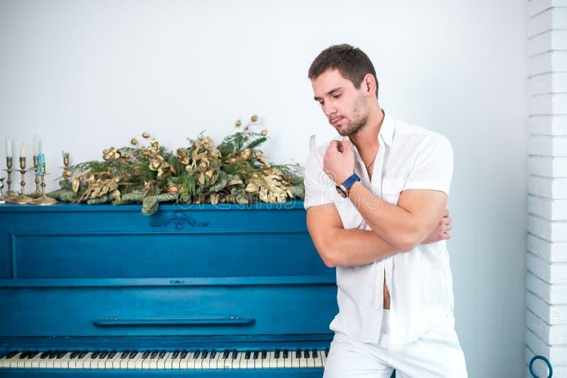 Nadenkende, knappe mens met een baard in witte kleren tegen de achtergrond van een piano, een geraspt overhemd met een naakt tors royalty-vrije stock foto