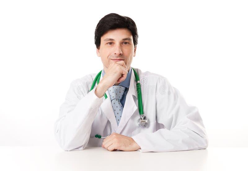 Nadenkende mannelijke arts met hand op kin stock fotografie