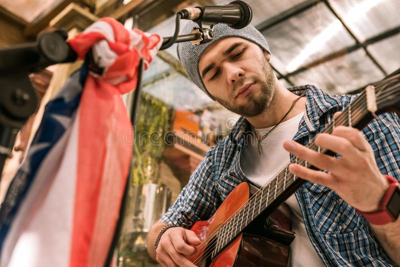 Nadenkende mannelijke gitarist die greep nieuwe snaar proberen royalty-vrije stock afbeeldingen