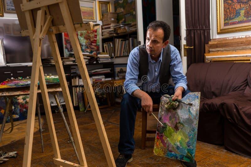 Nadenkende mannelijke kunstenaarszitting in een galerij stock foto's