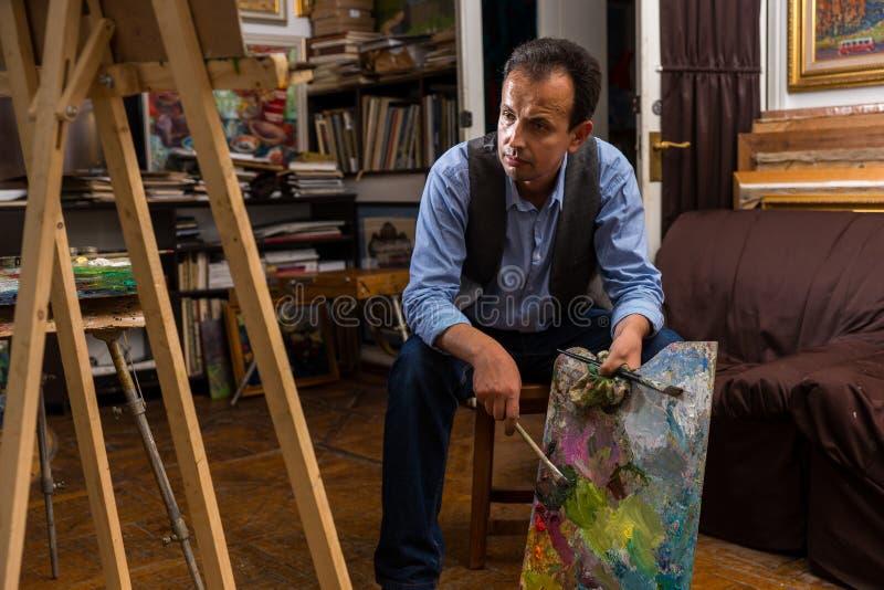 Nadenkende mannelijke schilderszitting in een studio royalty-vrije stock foto's