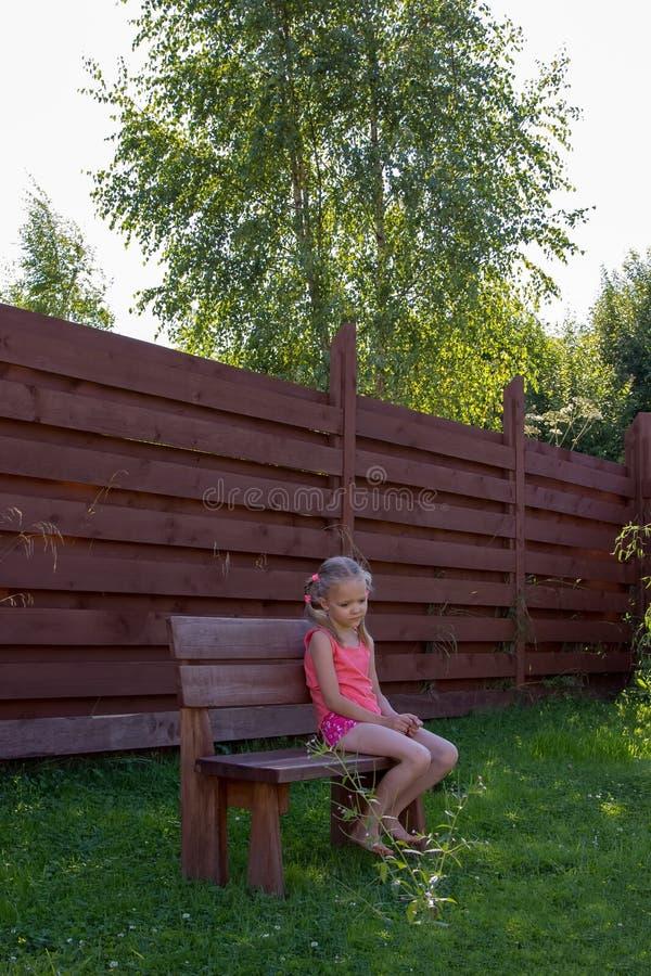Nadenkende meisjeszitting op houten bank royalty-vrije stock fotografie