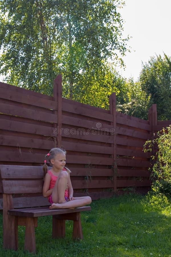 Nadenkende meisjeszitting op houten bank royalty-vrije stock afbeelding