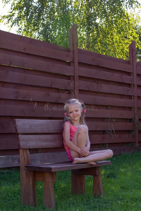 Nadenkende meisjeszitting op houten bank royalty-vrije stock foto
