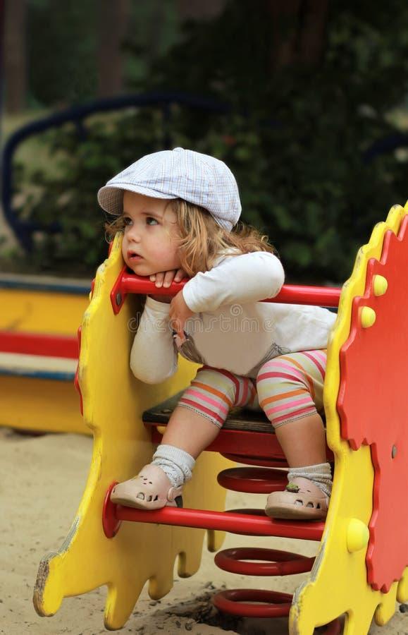 Nadenkende modieuze éénjarigenmeisje in een GLB die een stuk speelgoed egel berijden royalty-vrije stock afbeeldingen
