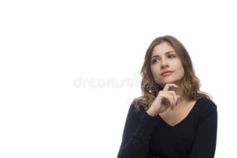 Nadenkende mooie jonge die vrouw, op witte achtergrond wordt geïsoleerd royalty-vrije stock afbeelding