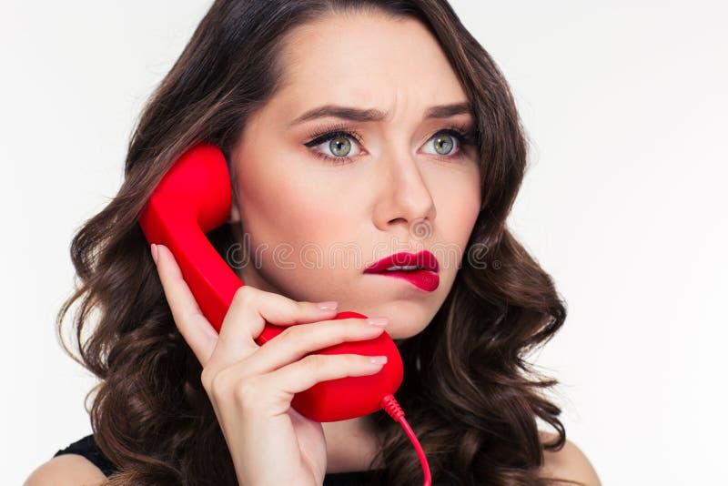 Nadenkende mooie krullende vrouw met retro kapsel die op telefoon spreken royalty-vrije stock afbeeldingen