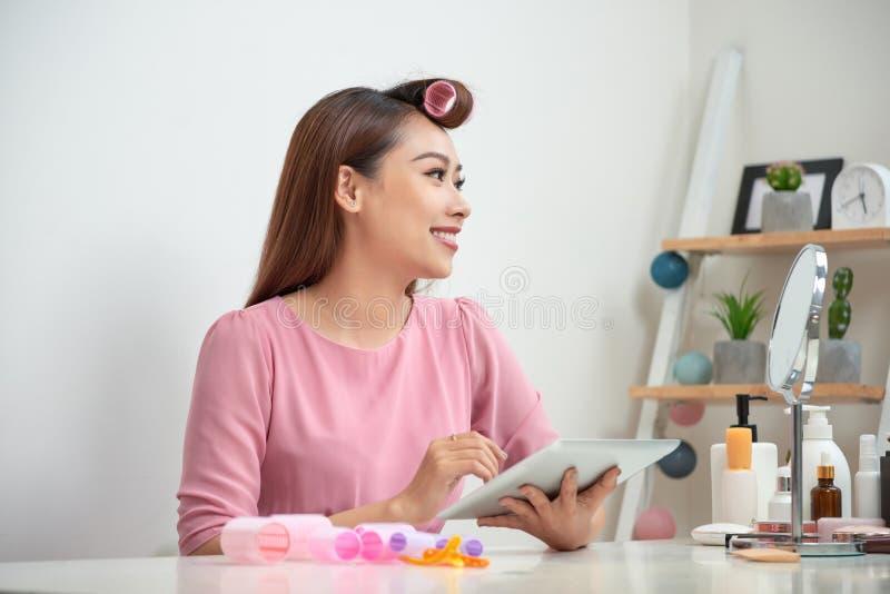 Nadenkende mooie vrouw die haarkrulspelden dragen die de zitting van tabletpc in woonkamer gebruiken royalty-vrije stock fotografie