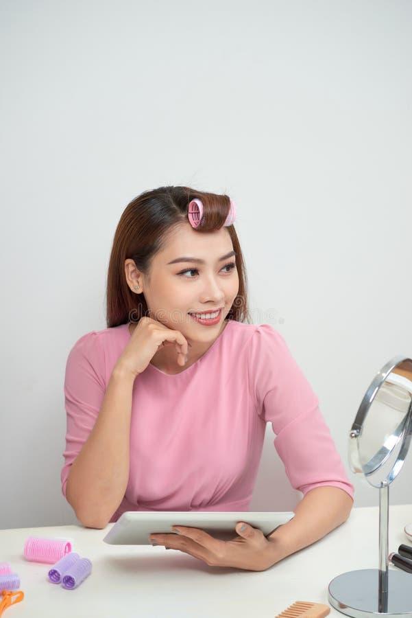 Nadenkende mooie vrouw die haarkrulspelden dragen die de zitting van tabletpc in woonkamer gebruiken royalty-vrije stock foto