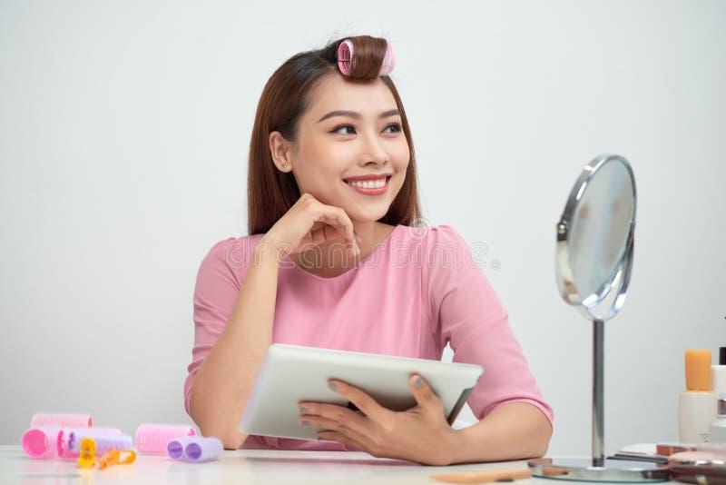 Nadenkende mooie vrouw die haarkrulspelden dragen die de zitting van tabletpc in woonkamer gebruiken stock afbeeldingen