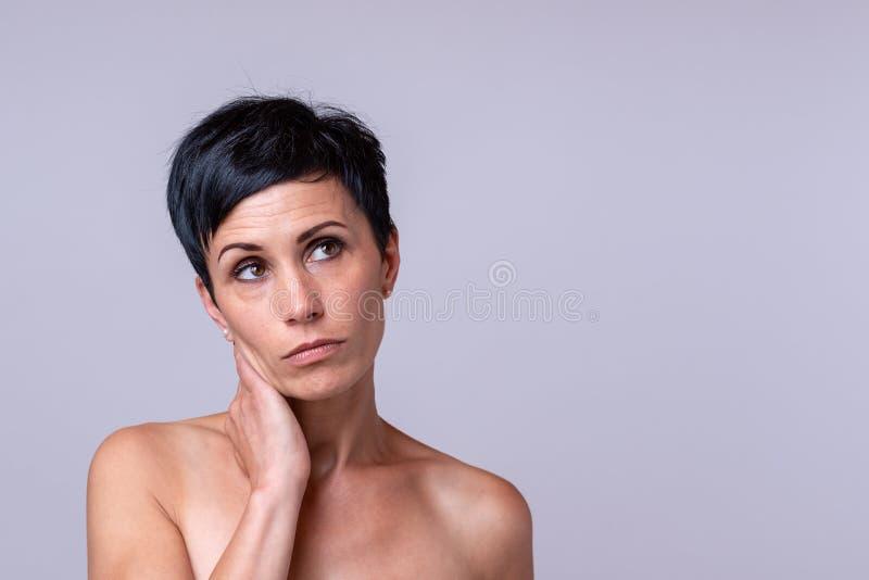 Nadenkende mooie vrouw met peinzende uitdrukking royalty-vrije stock foto
