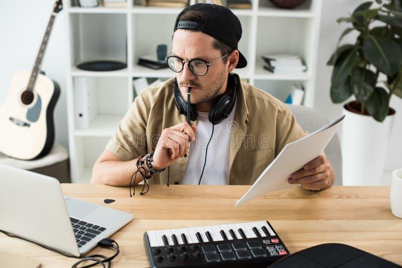 Nadenkende musicus die laptop bekijken stock foto's