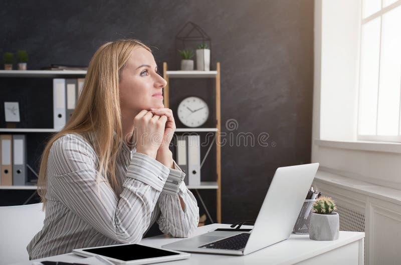 Nadenkende onderneemster die aan laptop op kantoor werken stock afbeeldingen