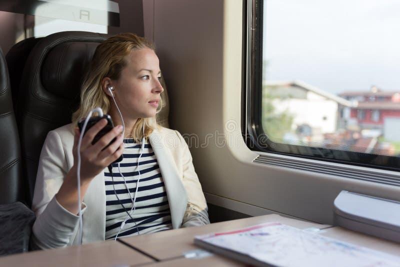 Nadenkende onderneemster die aan podcast op mobiele telefoon luisteren terwijl het reizen door trein stock afbeelding