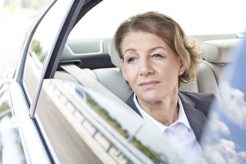 Nadenkende onderneemster die door venster kijken terwijl het zitten in auto stock foto
