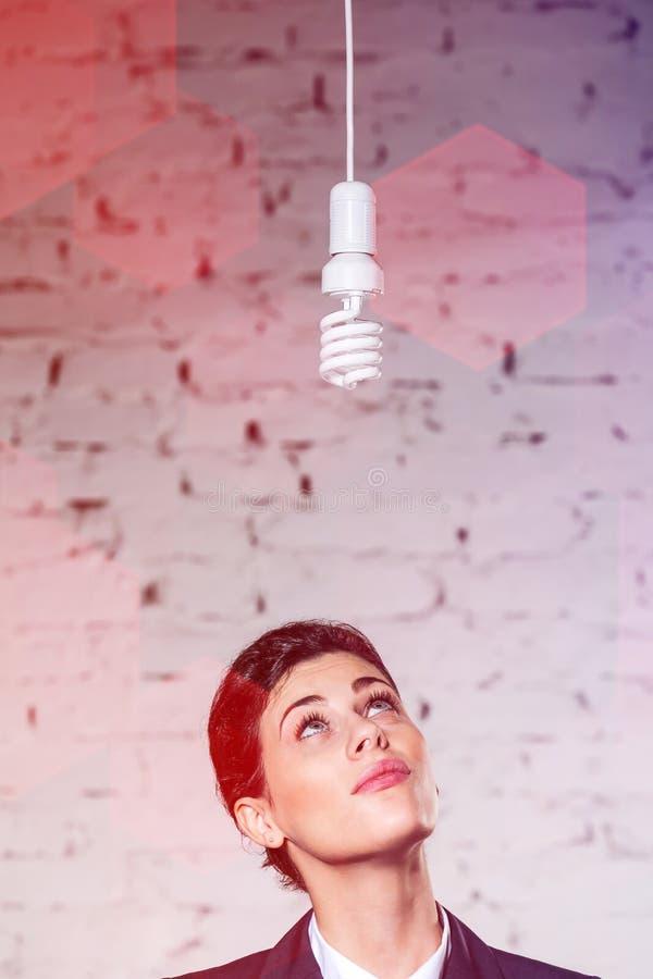 Nadenkende onderneemster die energie het efficiënte lightbulb hangen tegen bakstenen muur op kantoor bekijken stock fotografie