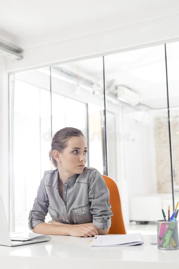 Nadenkende onderneemster die weg terwijl het zitten bij bureau kijken stock foto's