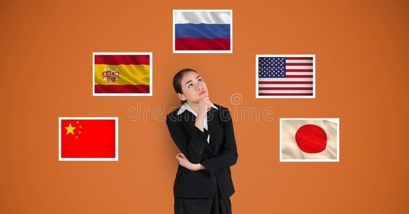 Nadenkende onderneemster die zich door vlaggen tegen oranje achtergrond bevinden stock foto's