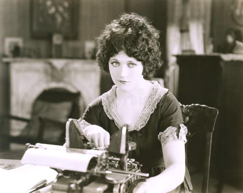 Nadenkende onderneemster met schrijfmachine bij bureau in bureau stock afbeelding