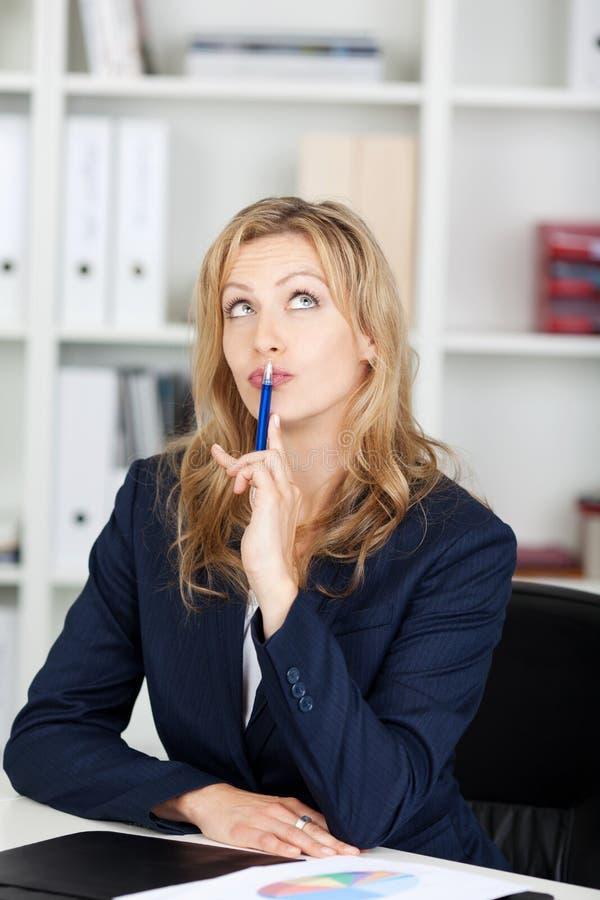 Nadenkende Onderneemster With Pen On Lips royalty-vrije stock foto