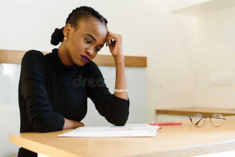 Nadenkende ongerust gemaakte Afrikaanse of zwarte Amerikaanse vrouw die haar voorhoofd met hand houden die blocnote in bureau bek royalty-vrije stock afbeeldingen