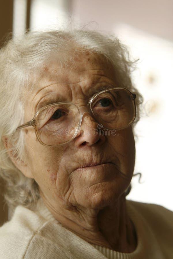 Nadenkende oude dame stock afbeelding