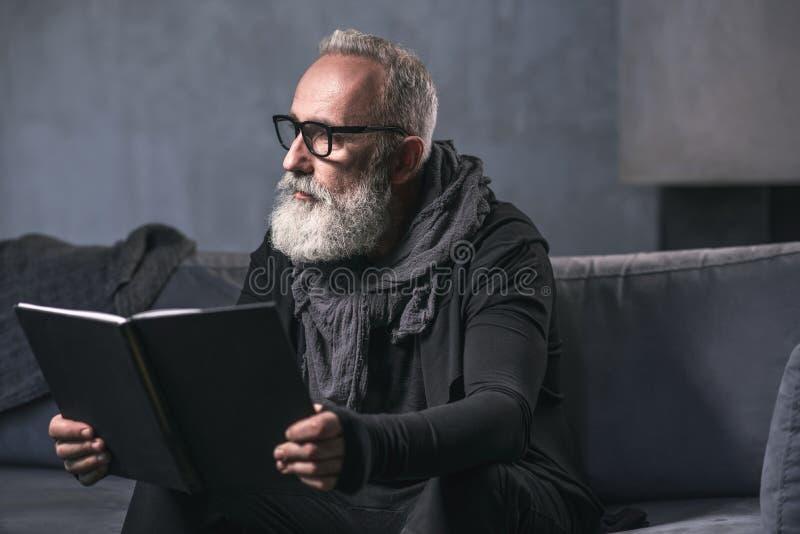 Nadenkende oude mens die interessant boek lezen royalty-vrije stock afbeeldingen