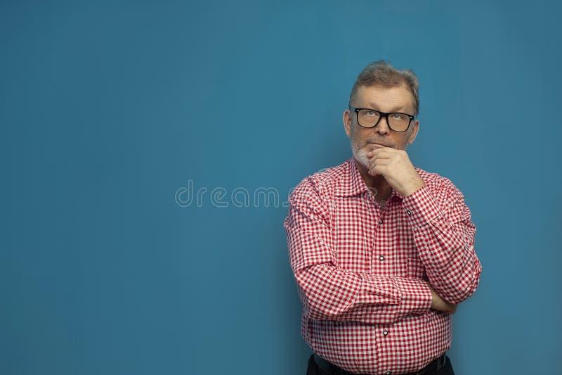 Nadenkende oude mens die slim toevallig overhemd en modieuze glazen dragen stock foto's