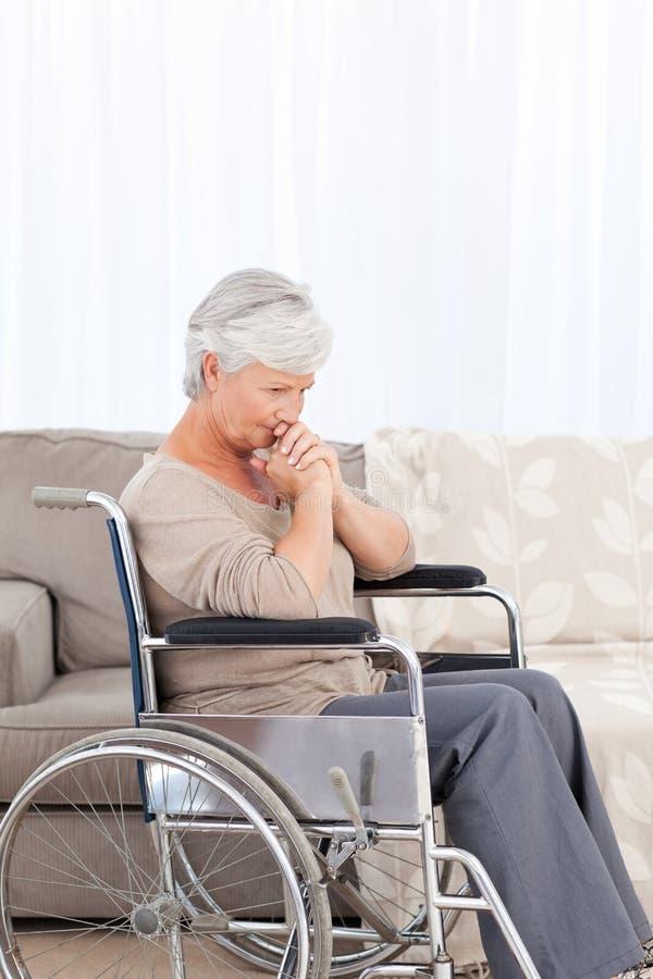 Nadenkende oudste in haar rolstoel stock afbeeldingen