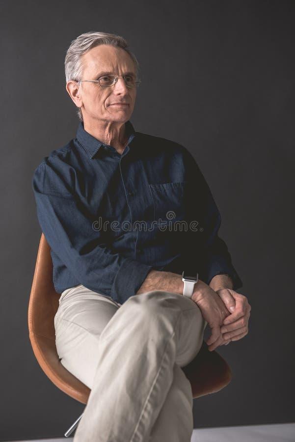 Nadenkende rijpe mannelijke plaatsbepaling op comfortabele zetel royalty-vrije stock afbeelding