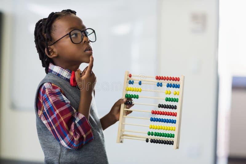 Nadenkende schooljongen die een wiskundetelraam in klaslokaal met behulp van stock fotografie