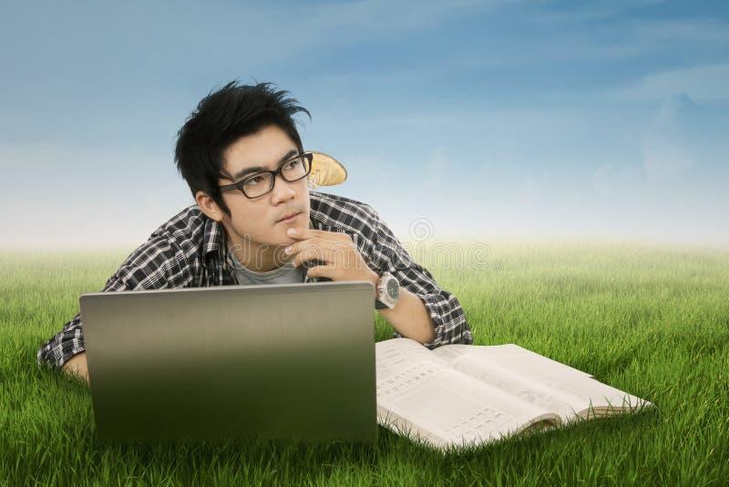 Nadenkende student in park 1 stock foto