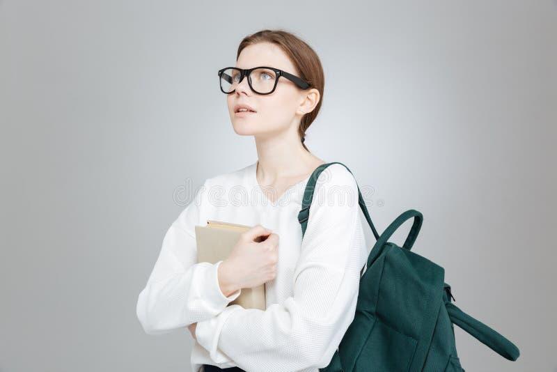 Nadenkende studente met rugzakholding boek en het denken stock foto