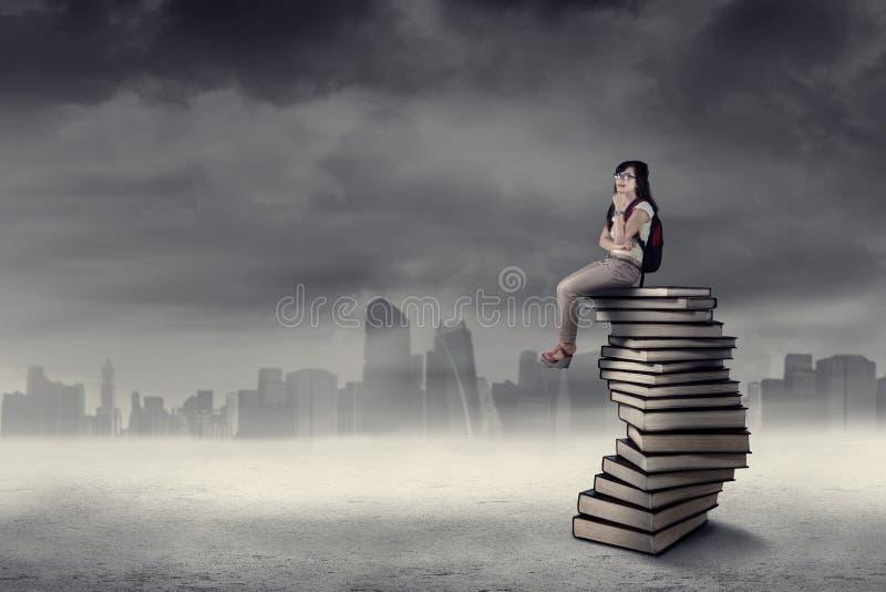 Nadenkende studentenzitting op boeken royalty-vrije stock afbeelding