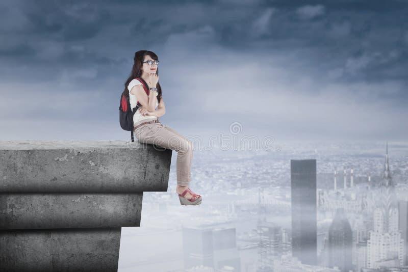 Nadenkende studentenzitting op hoog dak royalty-vrije stock afbeelding