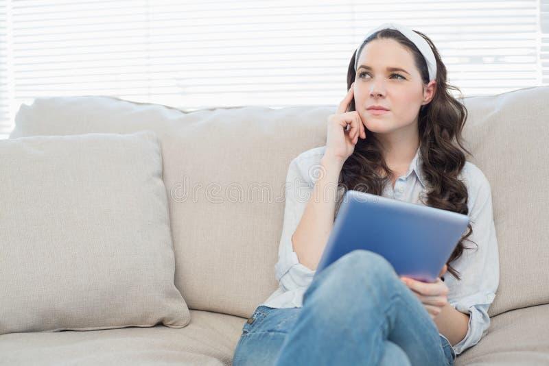 Nadenkende toevallige vrouw op comfortabele laag die tabletpc met behulp van royalty-vrije stock fotografie