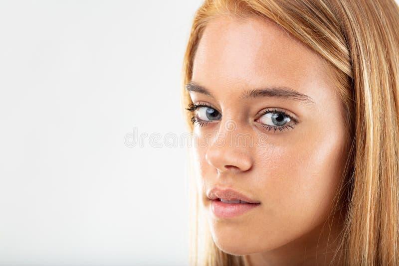 Nadenkende vrij jonge vrouw die aan camera draaien stock foto