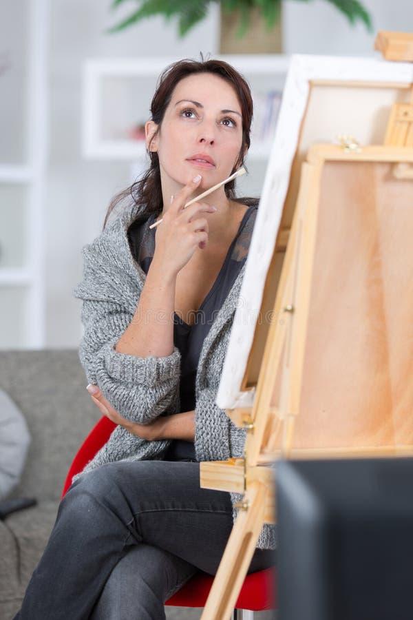 Nadenkende vrij jonge vrouwenkunstenaar die dichtbij het schilderen denken royalty-vrije stock afbeeldingen