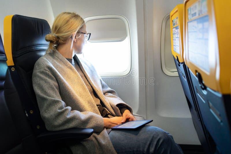 Nadenkende vrouw die door het venster kijken terwijl het reizen door vliegtuig royalty-vrije stock foto