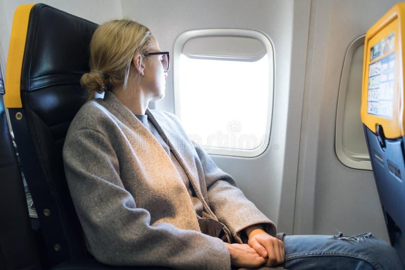 Nadenkende vrouw die door het venster kijken terwijl het reizen door vliegtuig royalty-vrije stock afbeeldingen