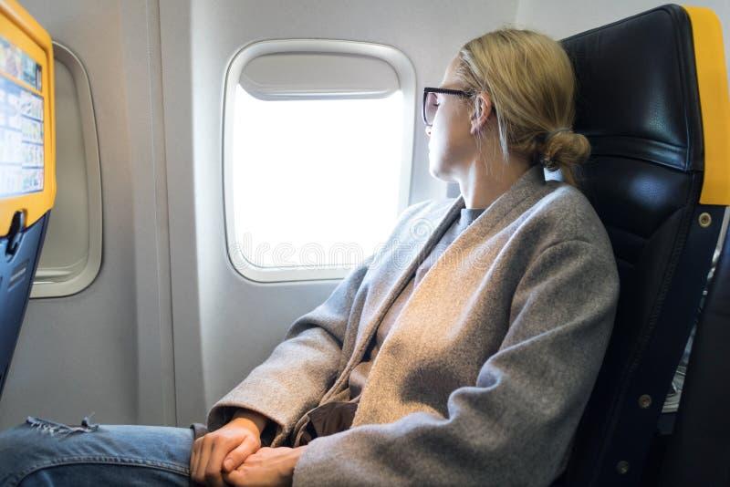 Nadenkende vrouw die door het venster kijken terwijl het reizen door vliegtuig royalty-vrije stock afbeelding