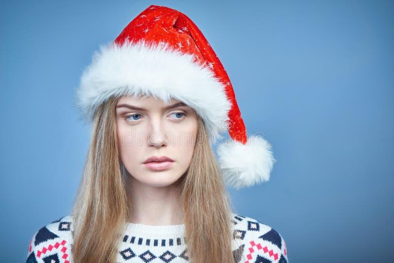 Nadenkende vrouw die Kerstmanhoed dragen die opzij eruit zien stock foto